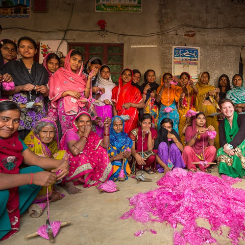 Dozens of our artisans in India (all women wearing brightly colored saris) are sitting in front of a large pile of pink fiber. These women are our yarn spinners and will spin this pile of pink fiber into our yarn by hand!