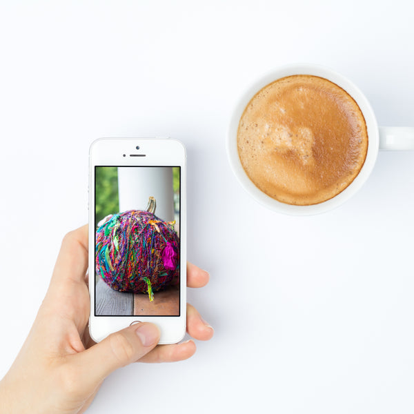 White mug filled with coffee, woman's hand holding a white cell phone with a yarn ball wallpaper, and a purple textbox that reads 'Digital Wallpaper Download' all on a white background