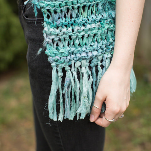 Close up of woman wearing black jeans and turquoise Silk Hippie Fringe Vest