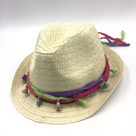 straw summer beach hat with silk ribbons tied around, sitting on a white background