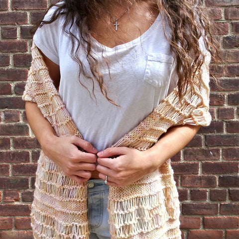 Close up of woman wearing a cream colored spring vibes shawl with a white tee and jeans in front of a brick wall