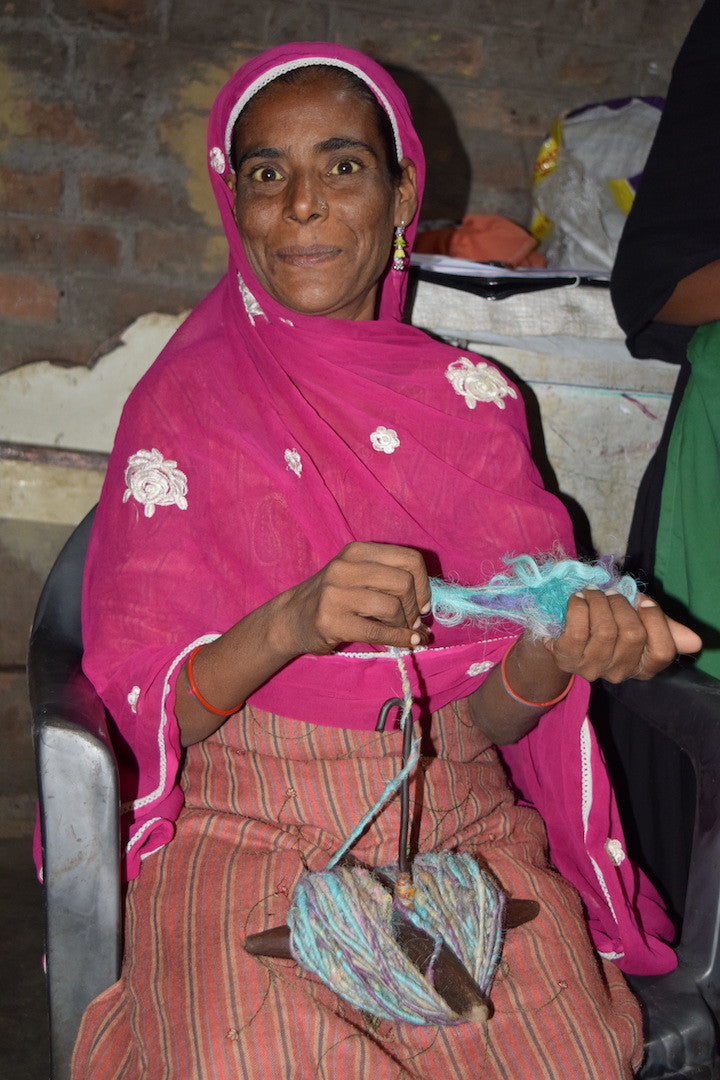 Woman wearing a pink sari and spinning blue yarn, sitting on a black chair