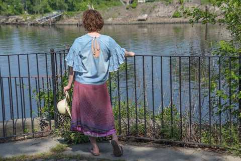 Woman wearing a sari wrap skirt and blue blouse standing in front of a fence in front of a body of water