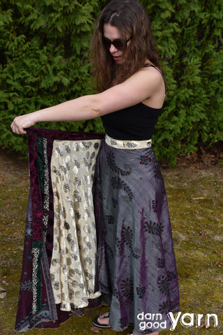 A model with long, brown hair is wearing dark sunglasses, a black top, and a gray skirt is standing on the grass in front of a large shrub. She is opening up one side of the skirt to show the reversible other side. The other side of the skirt is white and silver.