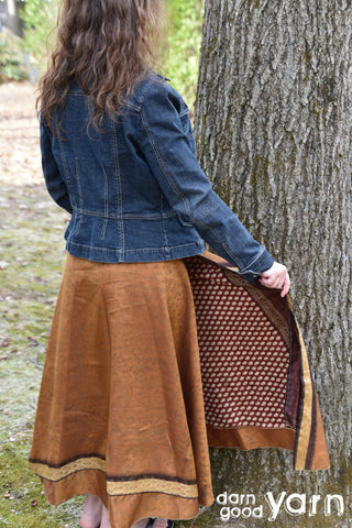 A model with long hair is facing away from the camera, staring at a large tree. They are wearing a long sleeved denim jacket and a golden skirt. One of their hands is showing the inside of the skirt, which is brown with an orange poka dot pattern.