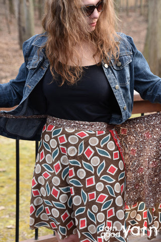 A model wearing sunglasses is sporting a denium jacket and a geometric patterned brown skirt. The skirt is mostly brown with red squares, blue leaf patterns, and white circles.