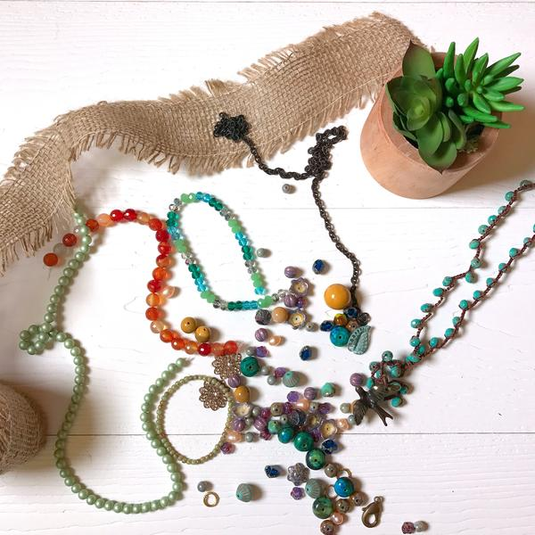 Multiple strands and loose glass beads in various shapes and colors strewn on a white surface next to a potted house plant and a bundle of burlap ribbon