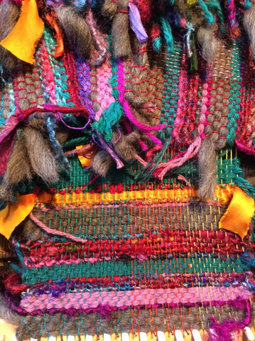 Close up of a multicolored striped and fringed woven yarn project