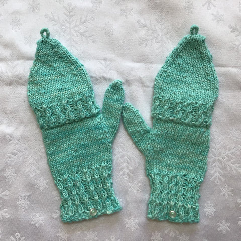 Finished knit mittens in teal on white tablecloth