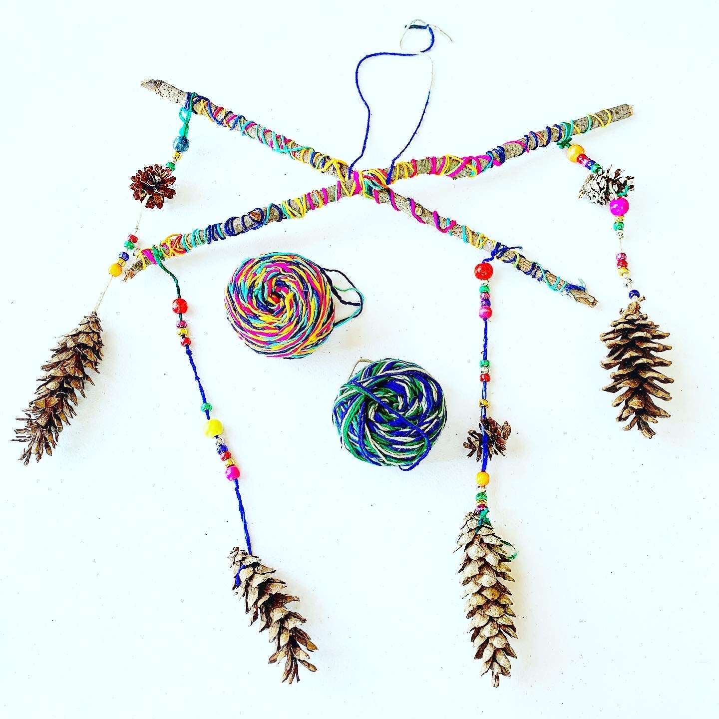 Finished pine cone mobile showing brightly colored branches hanging (4) pine cones with beaded yarn and two multicolored balls of yarn.