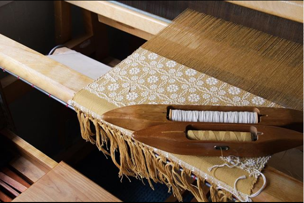 Close up of wooden weaving loom with mustard and white yarns