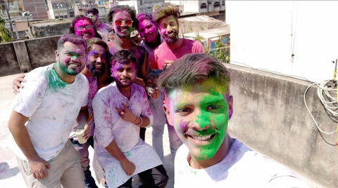 A group of young Indian people are taking a group selfie. The person taking the photo is the closest to the camera, and his group of friends are gathered together behind him. They are all wearing white clothes and are covered in the powered dye that is thrown around during festivals.