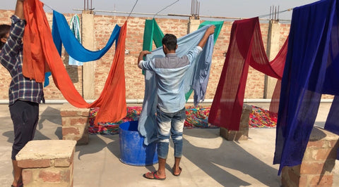 Two men are hanging up brightly colored sari fabric on a clothes line to dry.
