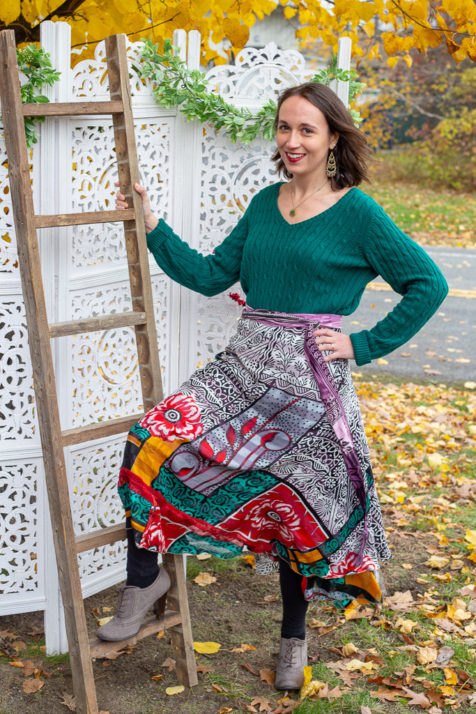 Woman wearing an oversized sweater and sari wrap skirt while standing in front of a white lattice backdrop and wooden ladder