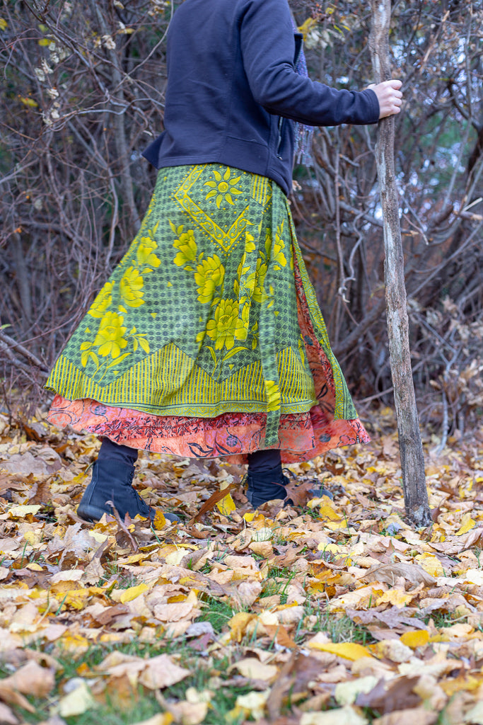 Woman wearing a sari wrap skirt and boots and walking through a wooded area