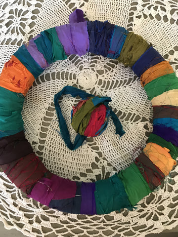 Multicolored ribbon-wrapped wreath next to matching ribbon on a white crochet doily background