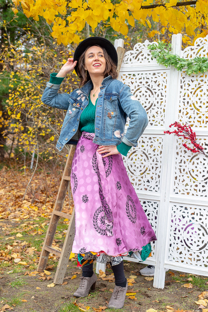 Woman wearing a sari wrap skirt, denim jacket, hat and boots while standing in front of a white lattice backdrop and a wooded area