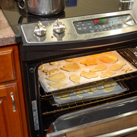 multiple sugar cookies on two cookie sheets inside of an oven