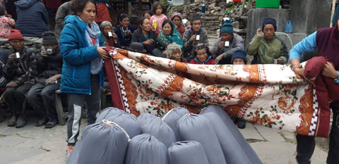 Beni displaying a blanket to a group of Nepalese people. There are about a dozen grey rucksacks, holding blankets, that Beni will distribute to those in need.