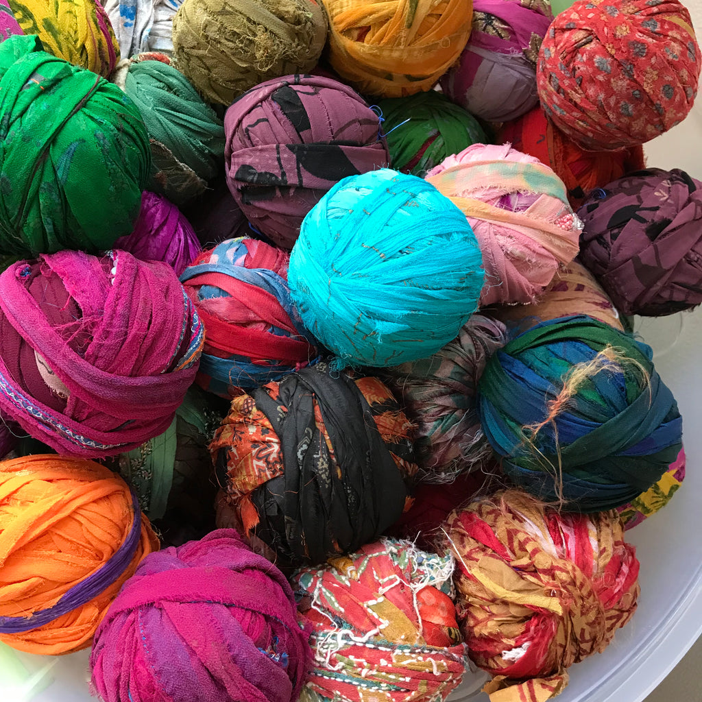 Multiple balls of multicolored yarn on a white background