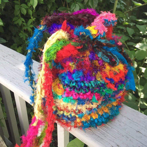 Tibetan Jewels Bucket Bag sitting on a wooden fence