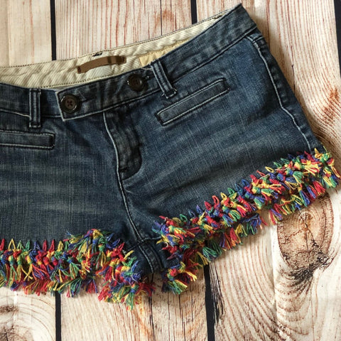 Denim shorts with crocheted multicolored edges sitting on a wooden surface