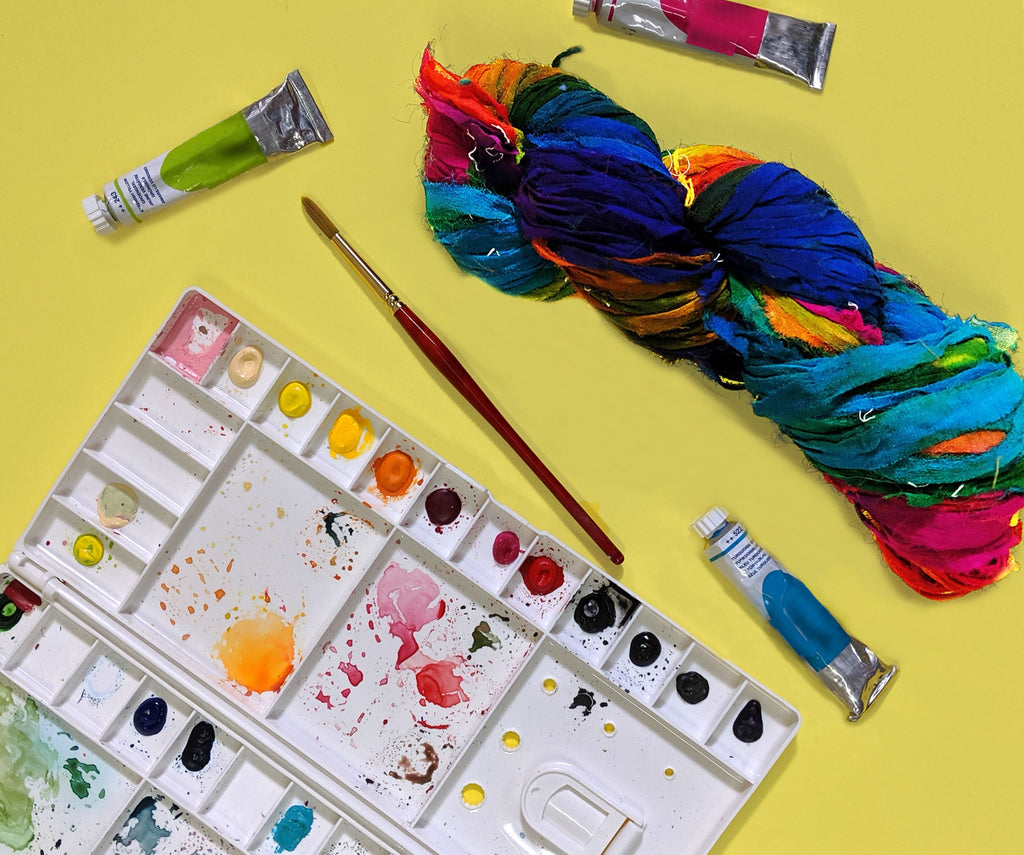 Tubes of paint, a white plastic container of watercolors, a paintbrush, and a multicolored skein of yarn on a yellow background