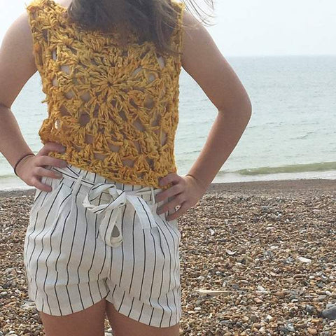 A person wearing a yellow tank top made out of DGY banana fiber yarn (colorway: sunflower). This person is on the beach.