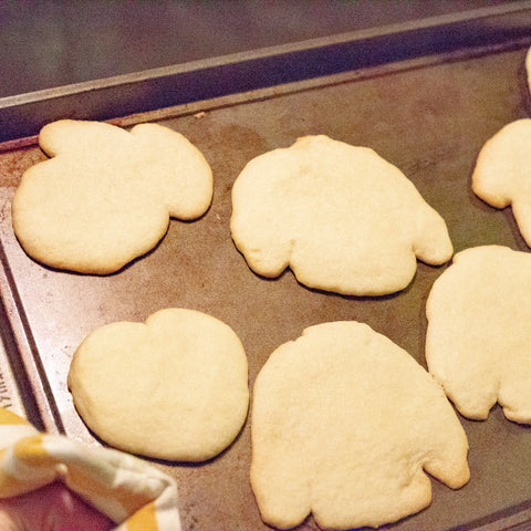 Baked sugar cookies in various shapes on a cookie sheet