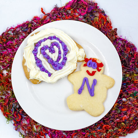 Two frosted sugar cookies on a white plate and knitted coaster
