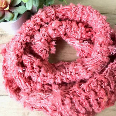 An infinity scarf made out of banana fiber (colorway: rich magenta) is curled into a cute spiral
