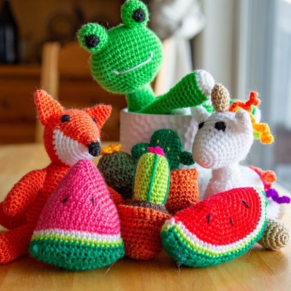 Amigurumi dolls in frog, unicorn, fox, cacti, and watermelon on a wooden table