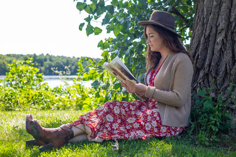 Woman wearing a sari wrap skirt and cardigan, hat, and books sitting next to a tree reading a book