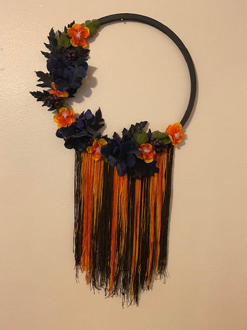 Another finished hoop, this one Halloween themed with a black hoop, spooky flowers, and orange and black yarn is hanging off the bottom half of the hoop, is now hanging on an off-white wall.