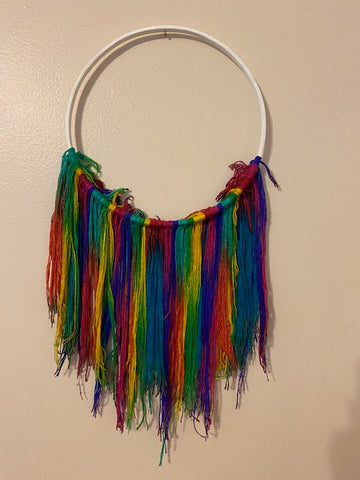 The finished white hoop, with multicolored yarn hanging off the bottom half of the hoop, is now hanging on an off-white wall.