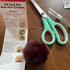 On a wooden table sits the instructions included in our DGY pom pom kits, a finished brown pom pom, and a pair of scissors.