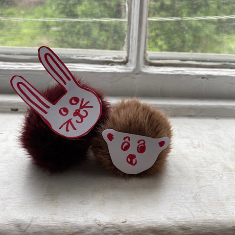 Two animal-faced pom-poms on a white window sill.