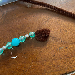 The brown pipe cleaner, now covered in the beads, is now folded at the ends so that the beads cannot slid off the pipe cleaner.