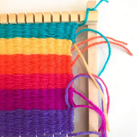 A multicolored work-in-progress is attached to the loom.  The order of the colors are: teal, yellow, orange, red, pink, and purple.