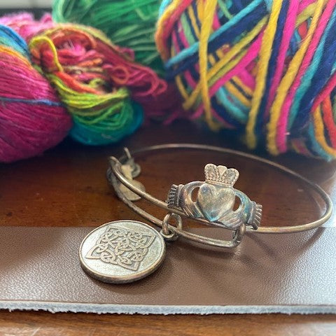 A silver ring, bracelet, and a leather wrist cuff are sitting on a wooden table. Behind them are a few different hanks and cakes of multicolored yarn.