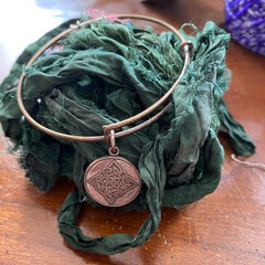 A silver bangle is sitting atop a pile of dark green sari ribbon yarn.