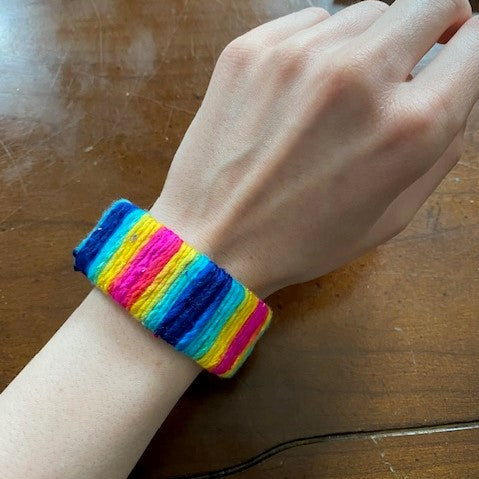 A person is now wearing the yarn-wrapped cuff around their wrist.