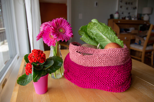 Market Tote Pink with Flowers in a vase and holding produce on a wooden surface