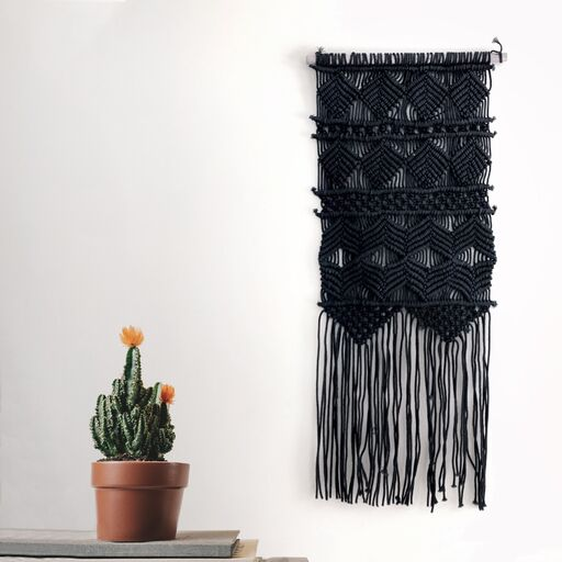 Black boho tapestry wall hanging on a white wall next to a potted cactus plant