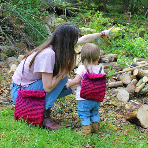 Woman and baby standing in grass next to a pile of wood and wearing matching pink crochet bags