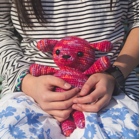 Pink Amigurumi Puppy stuffed animal held by little girl's hands