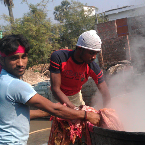Two Indian men are standing in front of a large boiling pot. This boiling pot is how the artisans dye the yarn and ribbons.