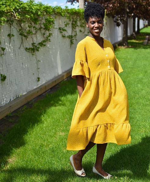 Woman wearing a yellow handmade dress and standing in grass in front of a white fence