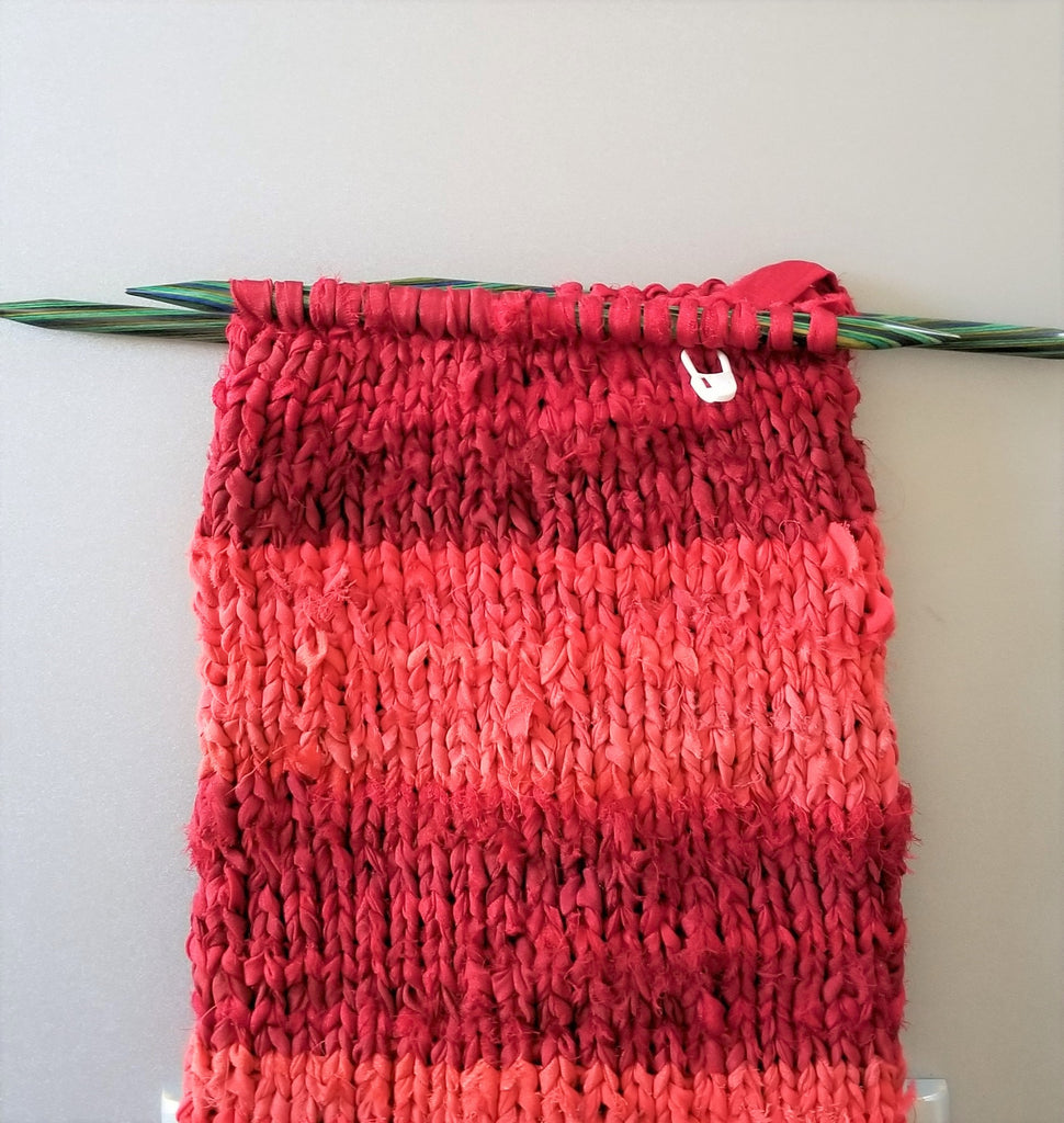 Red striped knit stocking with knitting needles on a white background