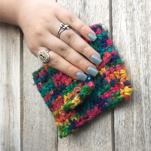 Woman's hand holding a rainbow crocheted coin purse over a wooden surface